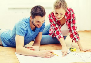 Couple sits on the floor and looks over plans for selling vs renovating